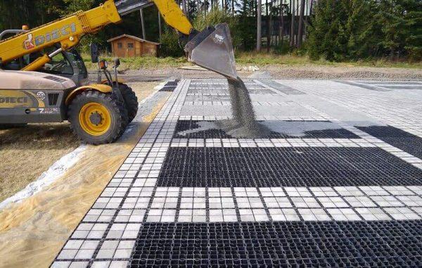 Заполнение ячеек газонной решетки погрузчиком